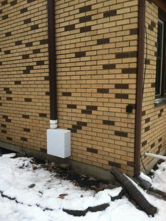 Radon mitigation device fixed to an external wall
